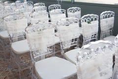 Sillas blancas con las flores para una ceremonia de boda Imagen de archivo libre de regalías