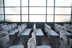 Sillas blancas con las flores para una ceremonia de boda Fotografía de archivo