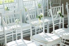 Sillas blancas con las flores para una ceremonia de boda Fotos de archivo
