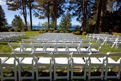 Sillas blancas del acontecimiento en jardín escénico por un lago Imagen de archivo