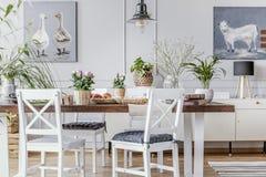 Sillas blancas en la tabla de madera con las flores en interior del comedor con los carteles y la lámpara Foto verdadera imagenes de archivo