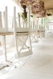 Sillas blancas en las tablas al revés en terraza del verano del café de la calle Imagenes de archivo