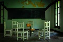 Sillas blancas en los círculos que rodean una silla anaranjada Tablero negro en la pared imágenes de archivo libres de regalías