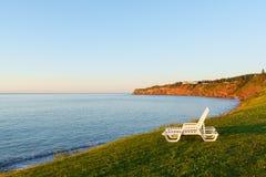 Sillas blancas por la orilla del golfo del santo Lorenzo Foto de archivo
