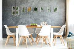 Sillas blancas por la tabla Imagen de archivo