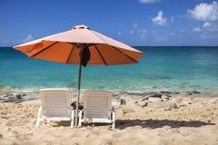 Sillas blancas y, paraguas en una playa Fotos de archivo libres de regalías