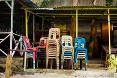 Sillas coloridas apiladas de una barra cerrada de la isla Fotografía de archivo libre de regalías
