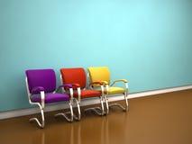 Sillas coloridas cerca de la pared azul Fotografía de archivo
