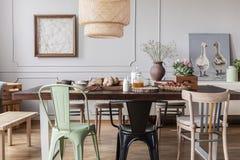 Sillas coloridas en la tabla de madera en interior gris del comedor con los carteles y las flores Foto verdadera imagen de archivo