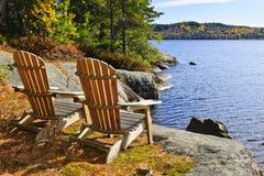 Sillas de Adirondack en la orilla del lago Imagen de archivo libre de regalías