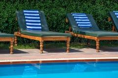 Sillas de cubierta cerca de la piscina Imagenes de archivo