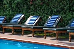 Sillas de cubierta cerca de la piscina Imágenes de archivo libres de regalías