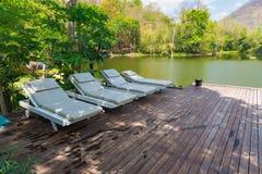 Sillas de cubierta de madera en el suelo de madera cerca del azul del lago y de la montaña Fotografía de archivo