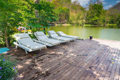 Sillas de cubierta de madera en el suelo de madera cerca del azul del lago y de la montaña Foto de archivo libre de regalías