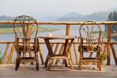 Sillas de cubierta de mimbre con café en una tabla y una opinión del lago Fotografía de archivo