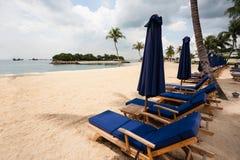 Sillas de cubierta en la playa de la isla de Sentosa en Singapur. Imagen de archivo libre de regalías