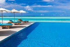 Sillas de cubierta y piscina del infinito sobre laguna tropical Fotos de archivo libres de regalías