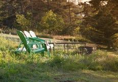 Sillas de jardín verdes por un hoyo del fuego fotografía de archivo