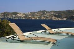 Sillas de la piscina en el agua Fotografía de archivo libre de regalías
