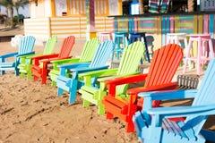 Sillas de madera coloridas en la playa Foto de archivo libre de regalías