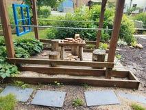 Sillas de madera del tocón de la tabla y de árbol y tejas de piedra en área de juego de niños en jardín Foto de archivo