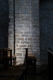 Sillas de madera en una iglesia oscura, iluminación sutil en la pared de piedra Fotos de archivo libres de regalías