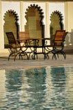 Sillas de madera por una piscina Imágenes de archivo libres de regalías