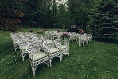 Sillas de mimbre blancas elegantes elegantes del vintage con las flores para un w Foto de archivo libre de regalías