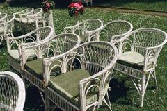 Sillas de mimbre blancas elegantes elegantes del vintage con las flores para un w Fotografía de archivo libre de regalías