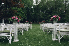 Sillas de mimbre blancas elegantes elegantes del vintage con las flores para un w Imagen de archivo libre de regalías
