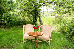 Sillas de mimbre con la tabla en el jardín Imagen de archivo