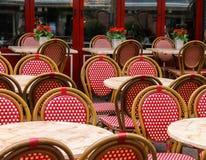 Sillas de mimbre rojas y blancas y pequeñas tablas en café al aire libre Foto de archivo libre de regalías