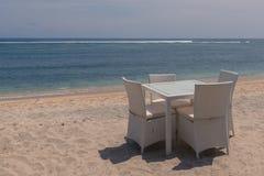 Sillas de mimbre y una tabla de cristal en la playa Foto de archivo libre de regalías