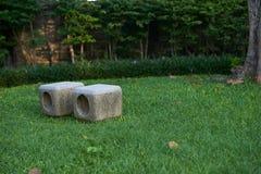 Sillas de piedra en hierba verde en parque o jardín en backgrou de la naturaleza imagen de archivo