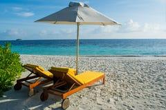 Sillas de playa amarillas en la playa tropical en Maldivas Fotografía de archivo