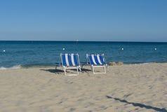 Sillas de playa azules en la playa vacía Imagen de archivo libre de regalías