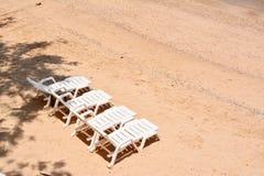 4 sillas de playa blancas Fotos de archivo