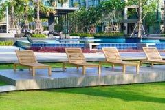 Sillas de playa cerca de la piscina en jardín Imagenes de archivo