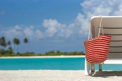 Sillas de playa con el bolso en la playa arenosa blanca Foto de archivo libre de regalías