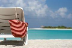Sillas de playa con el bolso en la playa arenosa blanca Fotografía de archivo libre de regalías