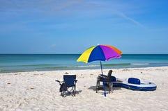 Sillas de playa con el paraguas y la balsa Imagen de archivo