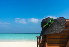 Sillas de playa con el sombrero en la playa arenosa blanca Foto de archivo