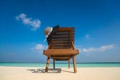 Sillas de playa con el sombrero en la playa arenosa blanca Foto de archivo libre de regalías