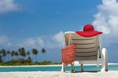 Sillas de playa con el sombrero en la playa arenosa blanca Fotografía de archivo