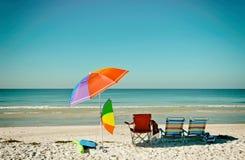Sillas de playa con los paraguas Foto de archivo