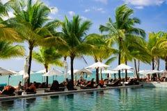 Sillas de playa con los paraguas cerca de la piscina contra el océano fotos de archivo