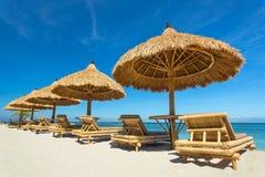 Sillas de playa con los paraguas de la paja en una playa hermosa Imagenes de archivo