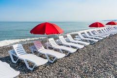 Sillas de playa o camas y paraguas rojos del sol en la playa Imagenes de archivo