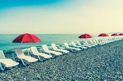 Sillas de playa o camas y paraguas rojos del sol en la playa Fotos de archivo