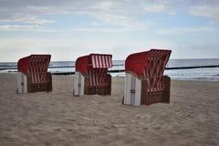 Sillas de playa o cestas alemanas típicas de las sillas de playa en la playa de Nord o del mar Báltico por la tarde Foto de archivo